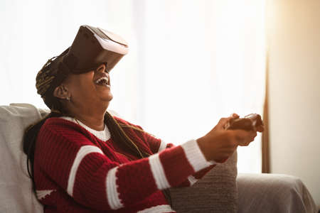 African senior woman having fun with new gaming virtual reality technology experience 写真素材