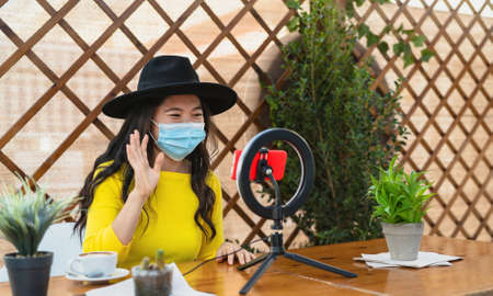 Happy Asian woman wearing face mask and vlogging online using smartphone cam and influencer led while drinking a coffee sitting in bar during corona virus outbreak