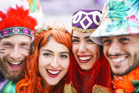 Happy friends celebrating carnival party outdoor - Portrait young crazy people having fun wearing funny costumes - Youth holidays culture lifestyle concept