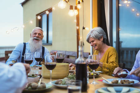 Happy senior friends having fun dining together on house patio - Elderly lifestyle people and food concept
