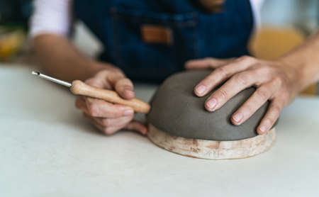 Close up female potter modeling clay bowl in workshop - Artisan work and creative craft concept