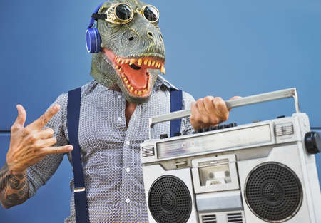 Crazy senior man having fun wearing t-rex mask while listening to music with headphones and vintage boombox stereo outdoor