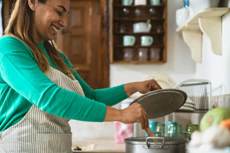 Latin mature woman cooking in old vintage kitchen - Smiling mother preparing lunch at home Standard-Bild