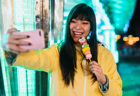 Asian girl taking selfie with mobile smartphone in amusement park - Youth social millennial people and technology trends concept Standard-Bild