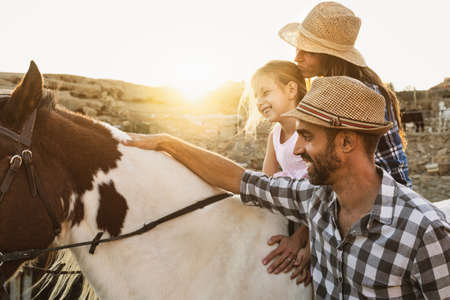 Happy mother daughter and father family having fun riding horse inside ranch Standard-Bild