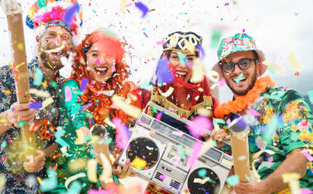 Young people wearing colorful costumes celebrating carnival party event throwing confetti outdoor