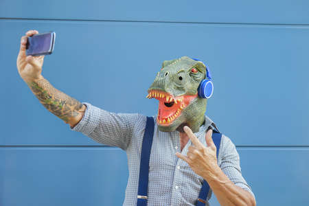 Crazy senior man wearing t-rex mask while taking selfie with mobile smartphone - Hipster male having fun listening music and dancing outdoor - Absurd surreal and technology concept