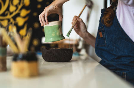 Woman potter painting clay pot in workshop - Artisan work and creative craft concept