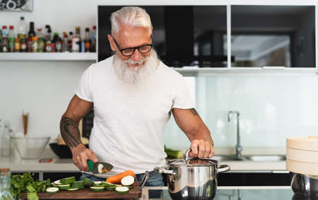 Happy senior man having fun cooking at home - Elderly person preparing health lunch in modern kitchen - Retired lifestyle time and food nutrition concept