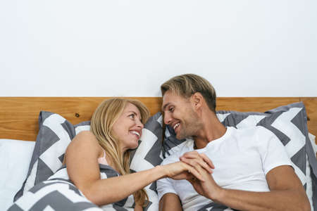 Happy smiling couple lying on bed having tender moments - Young people love and relationship concept Standard-Bild