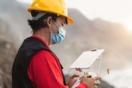 Male engineer monitoring the drone inspection while wearing face mask to avoid corona virus spreading - Technology and industrial concept