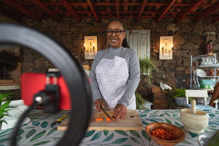 African senior woman preparing food recipe while streaming online with mobile smartphone cam for web kitchen masterclass channel