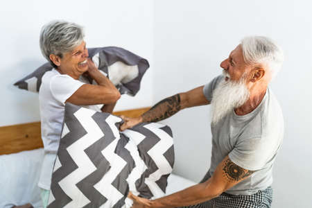 Happy senior couple having fun fighting with pillows in bed - Elderly lifestyle and love relationship concept