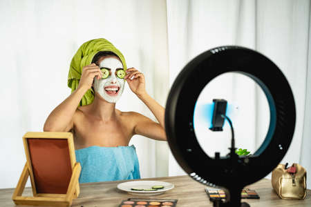 Young female vlogger applying skincare facial mask while streaming live for web channel at home - Happy girl having fun filming tutorial with mobile smartphone - Social influencer lifestyle concept Standard-Bild