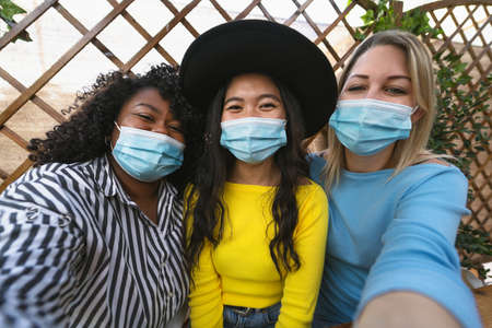 Multiracial friends wearing face mask while taking selfie with mobile smartphone cam during virus outbreak - Soft focus on central girl