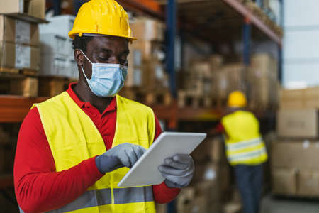Black man working in warehouse doing inventory using digital tablet and loading delivery boxes plan while wearing face mask during  virus pandemic - Logistic and industry concept