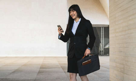 Asian business woman using mobile smartphone out the office - Entrepreneurship concept Standard-Bild