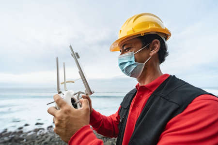 Male engineer monitoring the drone inspection while wearing face mask to avoid virus spreading - Technology and industrial concept