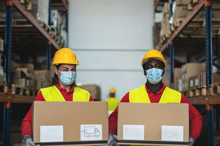 Team working in warehouse loading delivery boxes while wearing face surgical mask during corona virus pandemic - Logistic and industry concept