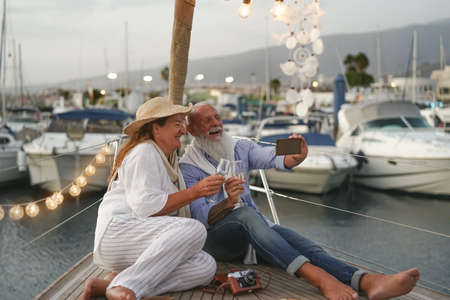 Senior couple toasting champagne while taking selfie on sailboat vacation - Happy mature people having fun celebrating wedding anniversary on boat trip - Love relationship and travel lifestyle concept