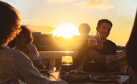 Young friends toasting with red wine at appetizer sunset time on patio house - Drink and food concept