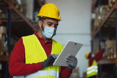 Young man working in warehouse doing inventory using digital tablet and loading delivery boxes plan while wearing face mask during  virus pandemic - Logistic and industry concept 版權商用圖片