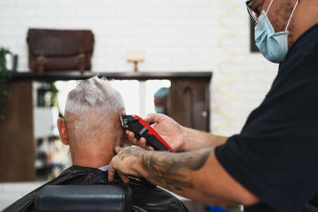 Male hairdresser cutting hair to hipster senior client while wearing face surgical mask - Young hairstylist working in barbershop during virus outbreak - Health care and haircut salon concept