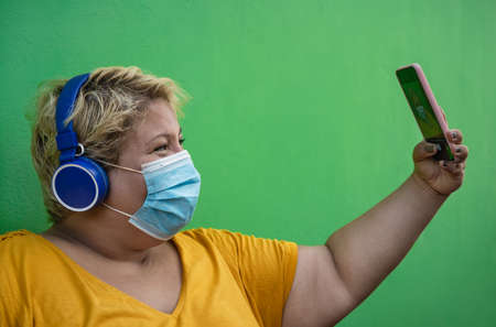 Plus size woman taking selfie with mobile smartphone and listening to music with wireless headphones while wearing face protective mask to avoid  virus infection - Health and technology concept