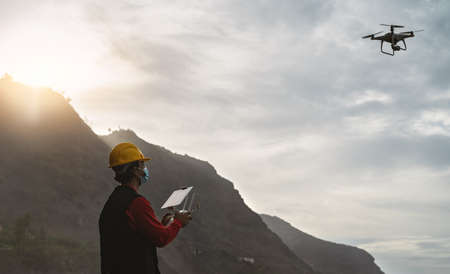 Male engineer doing inspection using drone while wearing face mask to avoid  virus spreading - Technology and industrial concept 版權商用圖片
