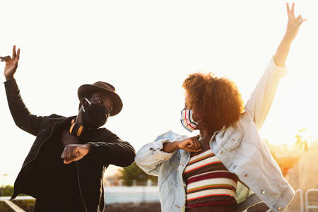 Afro American friends wearing face protective mask doing new social distance greetings bumping elbows - Youth millennial people and health care guidelines to avoid  virus spread 版權商用圖片