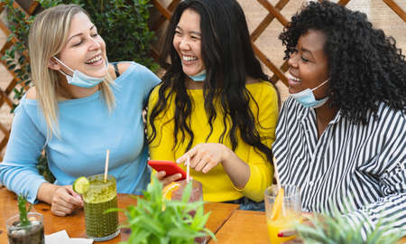 Multiracial friends watching on mobile smartphone while having healthy lunch in coffee brunch bar during  virus outbreak - Food and technology concept