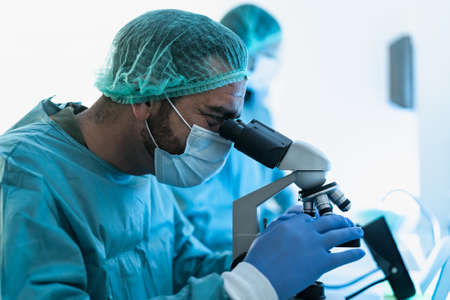 Scientist working in laboratory examining  through microscope - Science and technology concept