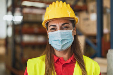 Happy Latin woman working in warehouse while wearing face mask during  virus pandemic - Logistic and industry concept 版權商用圖片