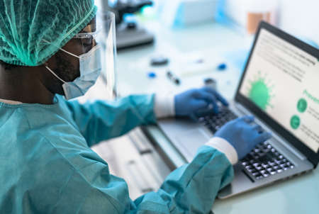 Medical worker wearing personal protective equipment using computer inside clinic during  virus outbreak - Research and development concept 版權商用圖片
