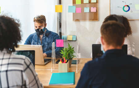 Young people in co-working creative space wearing surgical mask and keeping social distance to avoid  virus spread - Health care and business technology concept