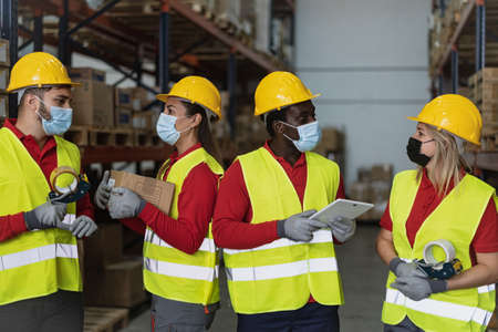 Team working together in warehouse doing inventory using digital tablet and loading delivery boxes while wearing face mask during  virus outbreak - Logistic and industrial concept 版權商用圖片