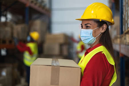 Latin woman working in warehouse loading delivery boxes while wearing face mask during  virus pandemic - Logistic and industry concept 版權商用圖片