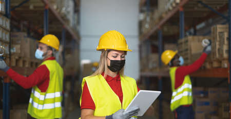 Team working in warehouse doing inventory using digital tablet and loading delivery boxes plan while wearing face mask during  virus outbreak - Logistic and industry concept