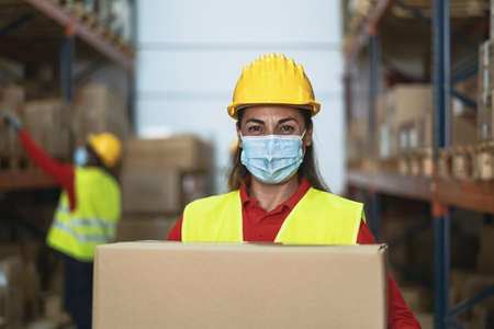 Latin woman working in warehouse carrying delivery boxes while wearing face mask during corona virus pandemic - Logistic and industry concept