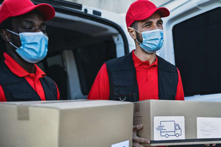 Young delivery men carrying cardboard box while wearing face mask to avoid corona virus spread - People working with fast deliver during corona virus outbreak
