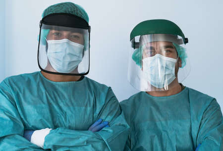 Doctors wearing personal protective equipment fighting against corona virus outbreak - Health care and medical workers concept