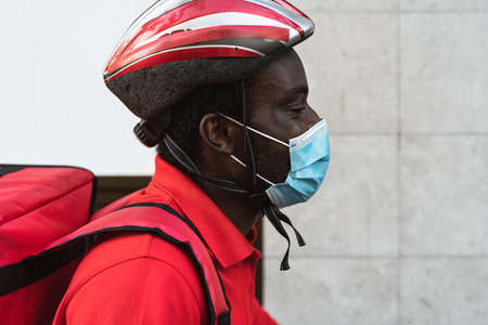 African rider man delivering meal to customers with electric bicycle while wearing face mask during corona virus outbreak - Ecological fast delivery food concept