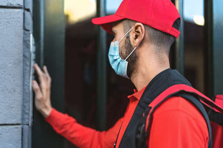 Rider man delivering meal to customers home while wearing face mask during   virus outbreak - Delivery food concept