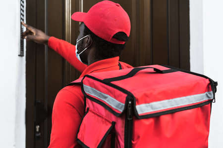 rider man delivering meal to customers home while wearing face mask during   virus outbreak - Delivery food concept 版權商用圖片