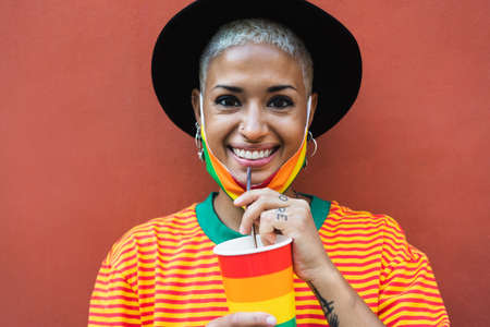 Young woman drinking cocktail during gay pride event - LGBT social movement concept