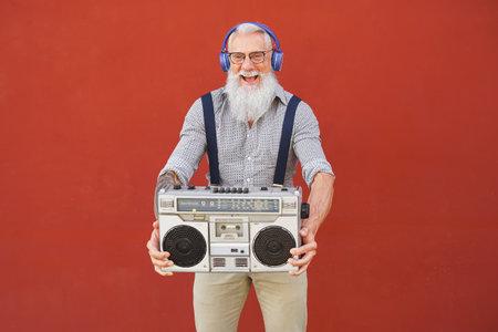 Happy senior man having fun listening to music with wireless headphones and vintage boombox outdoor 版權商用圖片