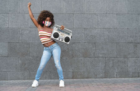 Young Afro woman wearing face mask dancing outdoor while listening to music with wireless headphones and vintage boombox stereo 版權商用圖片