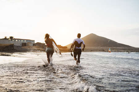 Happy surfers running in the water at sunset time - Young couple having fun surfing in ocean - Extreme sport and youth culture lifestyle concept 版權商用圖片