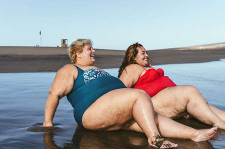 Happy overweight women having fun sitting on the beach during vacation - Curvy confident people lifestyle concept