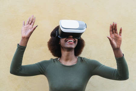 Afro woman using virtual reality glasses outdoor - Happy young girl having fun with innovated vr googles technology - Tech lifestyle entertainment and 3d game experience concept